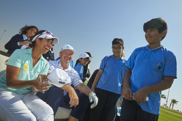 Maha Haddioui and Ernie Els sign caps for visiting kids at Royal Greens Golf and Country Club