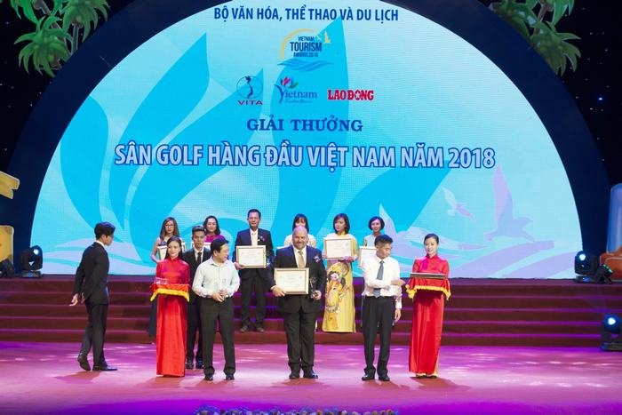 """Mr. Tran Van Thuat (right), Vice President of Vietnam General Confederation of Labour and Mr. Vuong Duy Bien (left), Deputy Minister of Ministry of Culture, Sport and Tourism give awards to Mr. Timothy Kevin Haddon (middle), General Manager of Ba Na Hills Golf Club."""