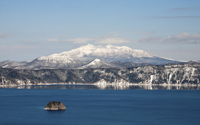 View of the mountains overlooking crater lake, Lake Mashu, Hokkaido, Japan.