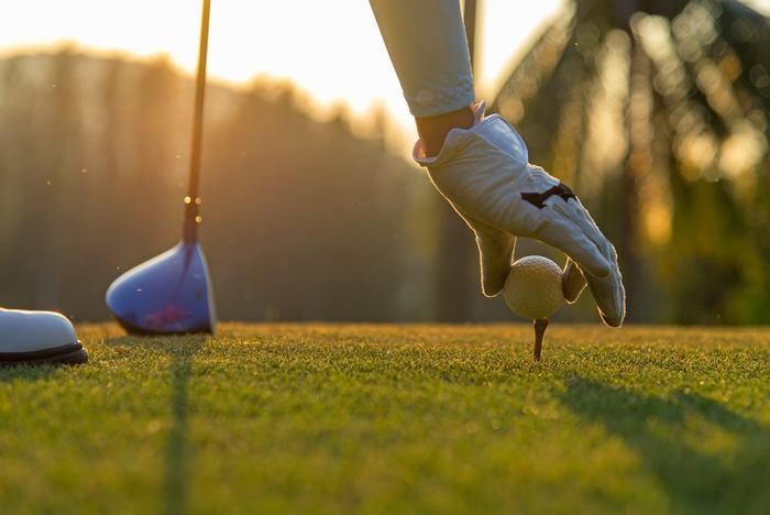golfer-putting-ball-on-tee